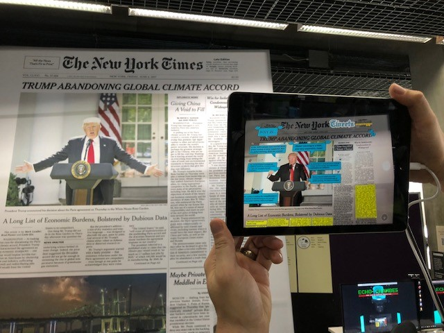 Interactive art work displaying Donald Trump which appears animated when viewed with tablet in the foreground.